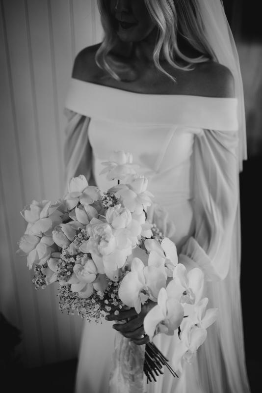 Real bride Hannah wears the long sleeve off shoulder wedding dress, Lauren with orchid bouquet