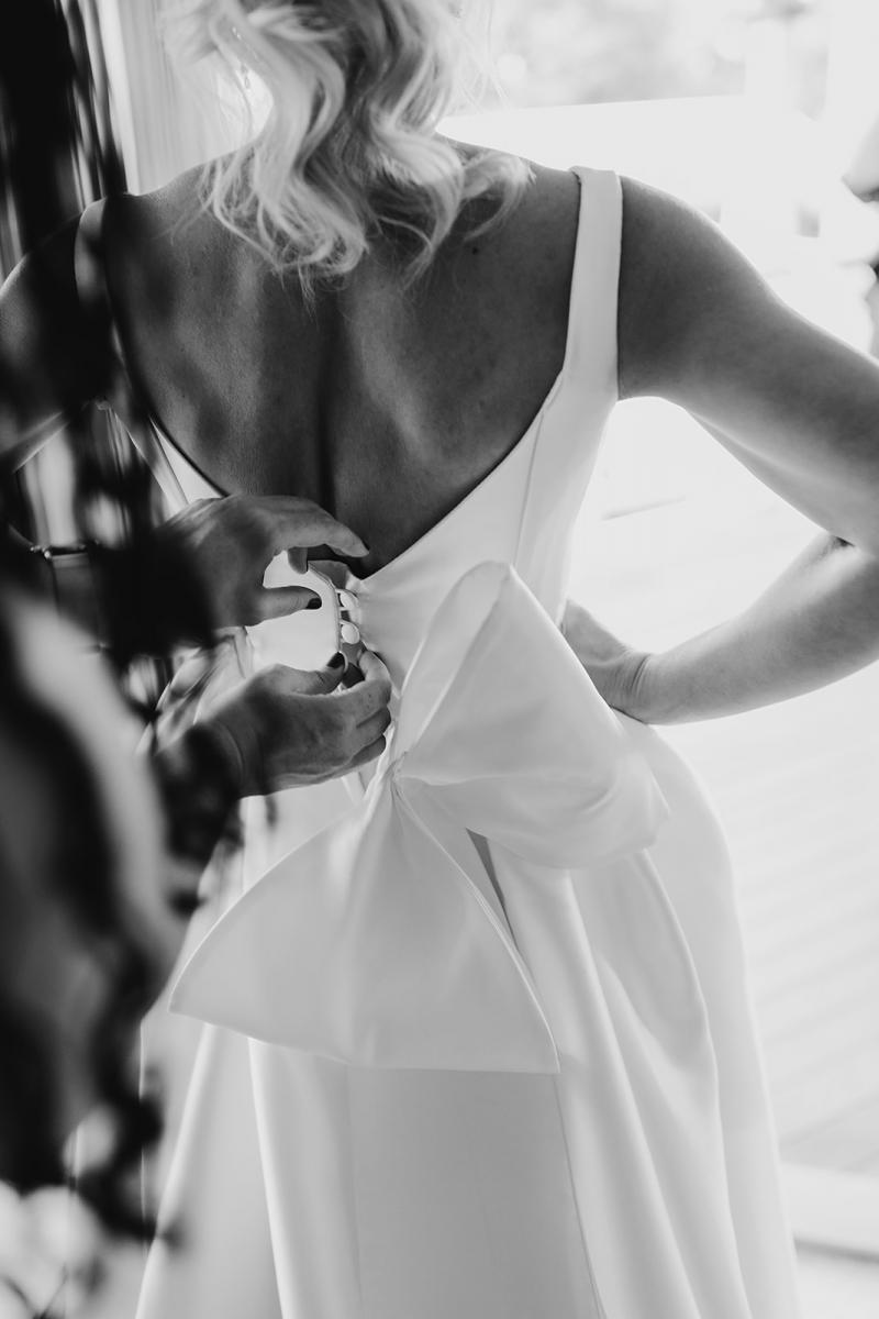 Real bride Caroline getting ready for her wedding, wearing the Taryn Camille gown with custom bow; a modern a-line wedding dress by Karen Willis Holmes.