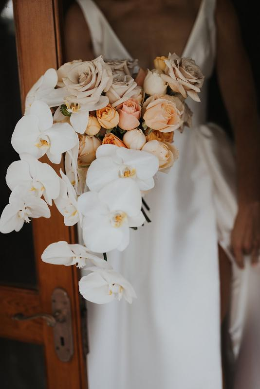 Floral orchid bouquet held by real bride Caroline