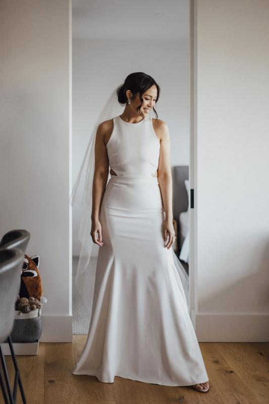 Real bride Melissa getting ready for beach wedding, wearing the Bridget gown; a relaxed casual wedding dress with a halter neckline and flattering shape by Karen Willis holmes.