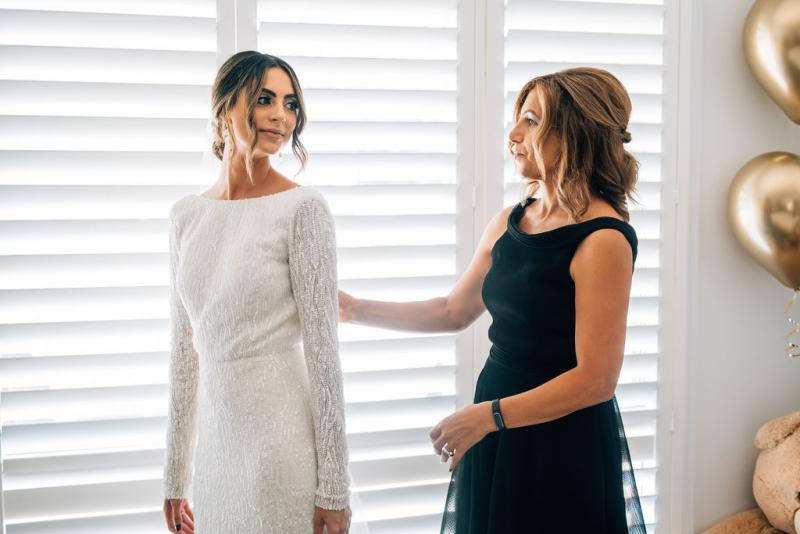 Real bride Katrina getting ready for wedding with Mother of bride, wearing the Margareta gown, a long sleeve backless wedding dress Karen Willis Holmes.