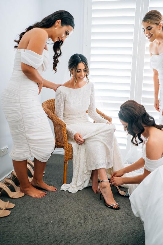 Real bride Katrina getting ready for wedding with bridesmaids, wearing the Margareta gown, a long sleeve backless wedding dress Karen Willis Holmes.