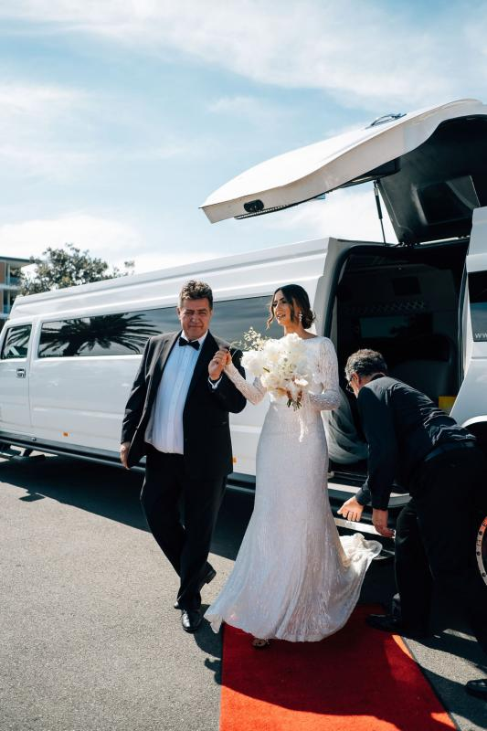 Real bride Katrina arriving to church wedding in white hummer, wearing the Margareta gown, a long sleeve wedding dress by Karen Willis Holmes.