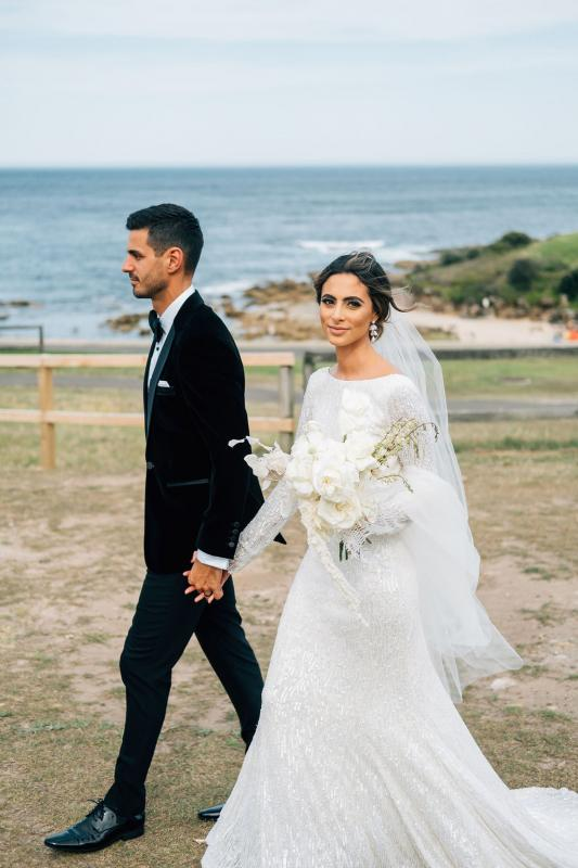Real bride Katrina at beach wedding wearing the Margareta gown from Karen Willis Holmes' Luxe collection; a long sleeve beaded wedding dress.
