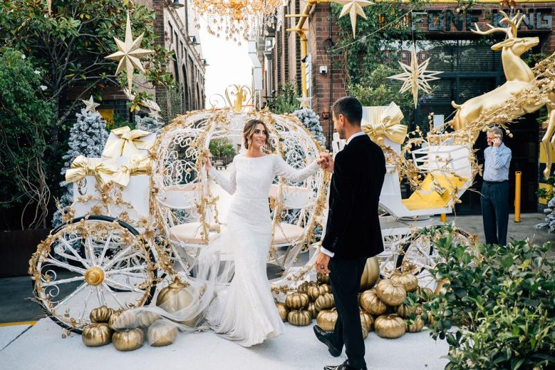 Real bride Katrina in front of Cinderella style carriage at the grounds of Alexandria, wearing the Margareta gown; a long sleeve backless wedding dress by Karen Willis Holmes