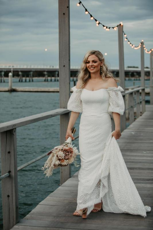 Real bride Kacie-Lee wears the Vivienne gown; a puff sleeve lace wedding dress by Karen Willis Holmes to beach wedding with natural toned bridal blooms.