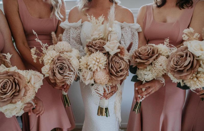 Real bride Kacie-Lee poses with bridesmaids wearing blush dresses, bride wearing the Vivienne gown by Karen Willis Holmes holding natural toned bridal blooms.