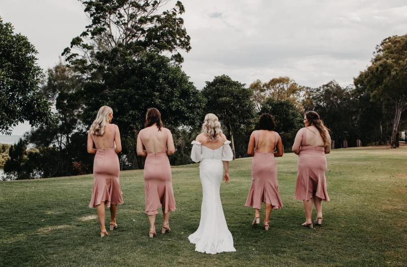 Real bride Kacie-Lee poses with bridesmaids wearing blush dresses, bride wearing the Vivienne gown by Karen Willis Holmes.