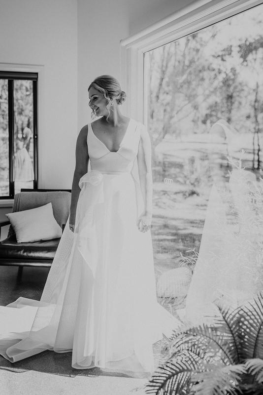 Real bride Samantha getting ready for her wedding, wearing the Aisha gonw; a v-neck A-line wedding dress with floral details by Karen Willis Holmes.