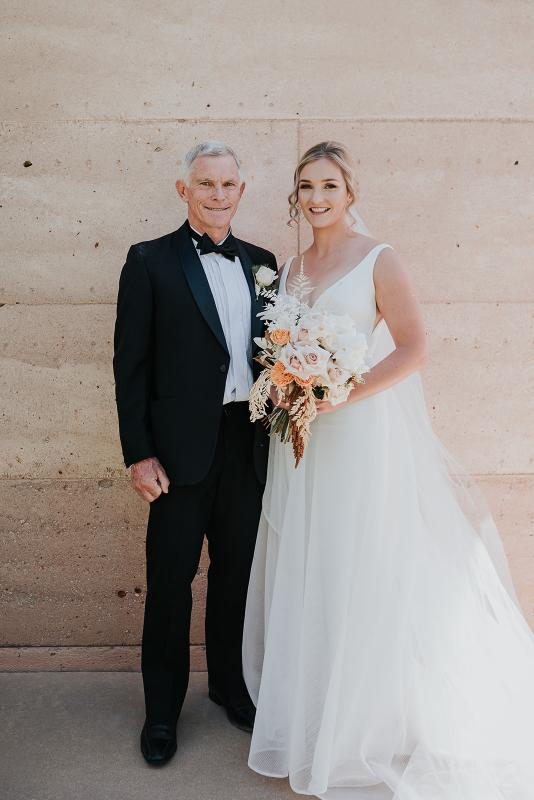 Real bride Samantha poses with Father wearing the Aisha gown by Karen Willis Holmes with bright coloured bouquet.