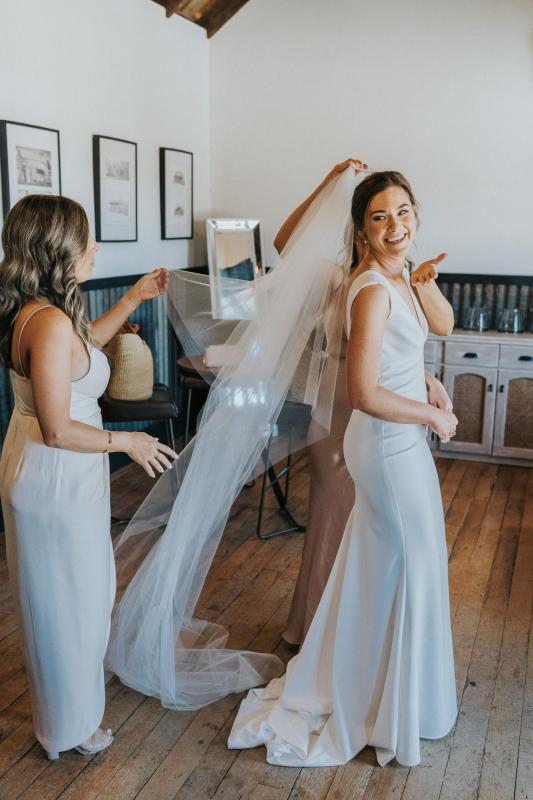 Real Bride Kate gets ready with her bridesmaids as they place her veil on her head. She wears the Arbella dress by KWH.