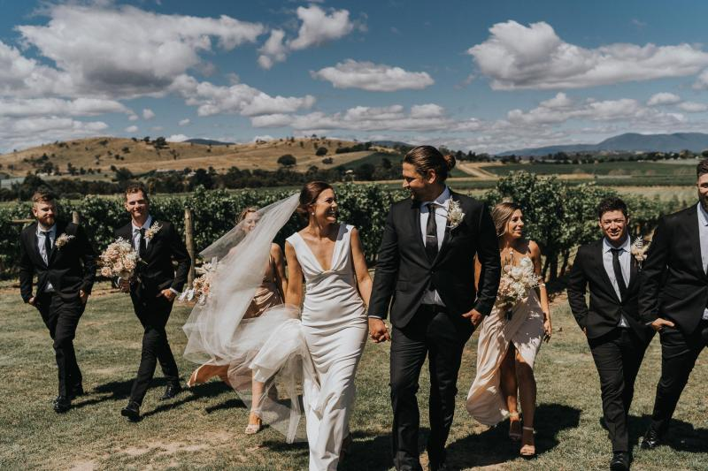 Newly weds, Kate and Mik, walk through the rustic landscape holding hands leading their group of bridesmaids and groomsmen to the reception. Kate wears the plunging v-neck Arabella gown by KWH.