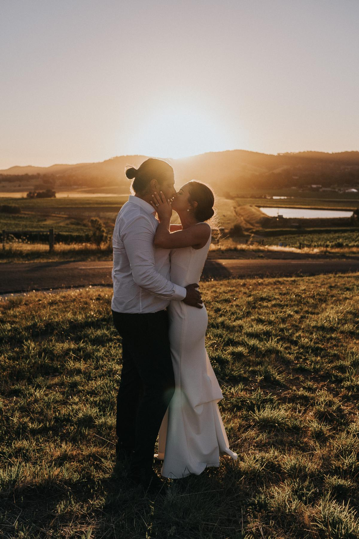 KWH Real bride Kate and Mik kiss in front of the sunset as she wears the modern, sleek, Arabella gown by KWH.