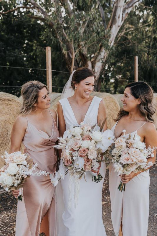 KWH real bride Kate laughs with her bridesmaids as they hold their blush and coral bouquets. Kate wears the moderns crepe Arabella dress.