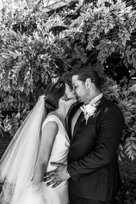 Real bride Kate and Mik kiss in front of a lush bush; she wears the crepe Arbella gown with plunging neckline by KWH.