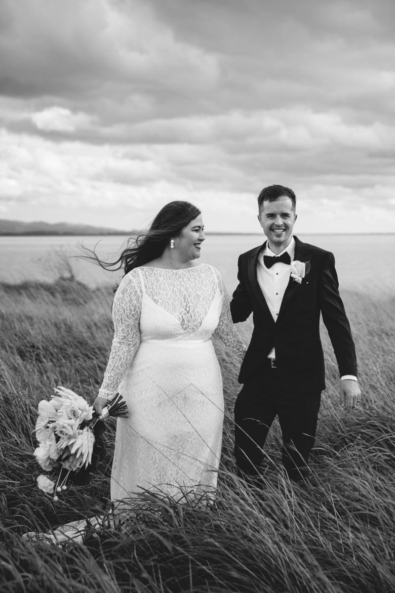 Real bride Jarna and husband Angus hold hands in dramatic Wellington landscape while she wears a long sleeve lace dress which is part of the CURVE collection.