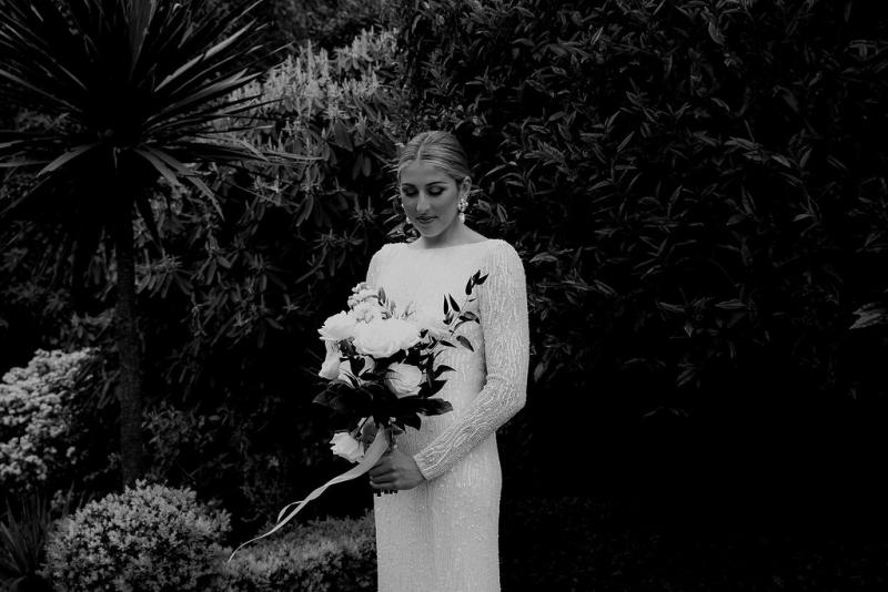 Real bride Hannah standing with her white bridal bouquet while wearing the beaded Margareta gown by KWH in this black and white photograph.