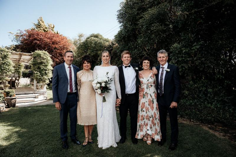 KWH Real bride Hannah and Angus stand with their family for wedding photos. The bride wears the long beaded Margareta gown.
