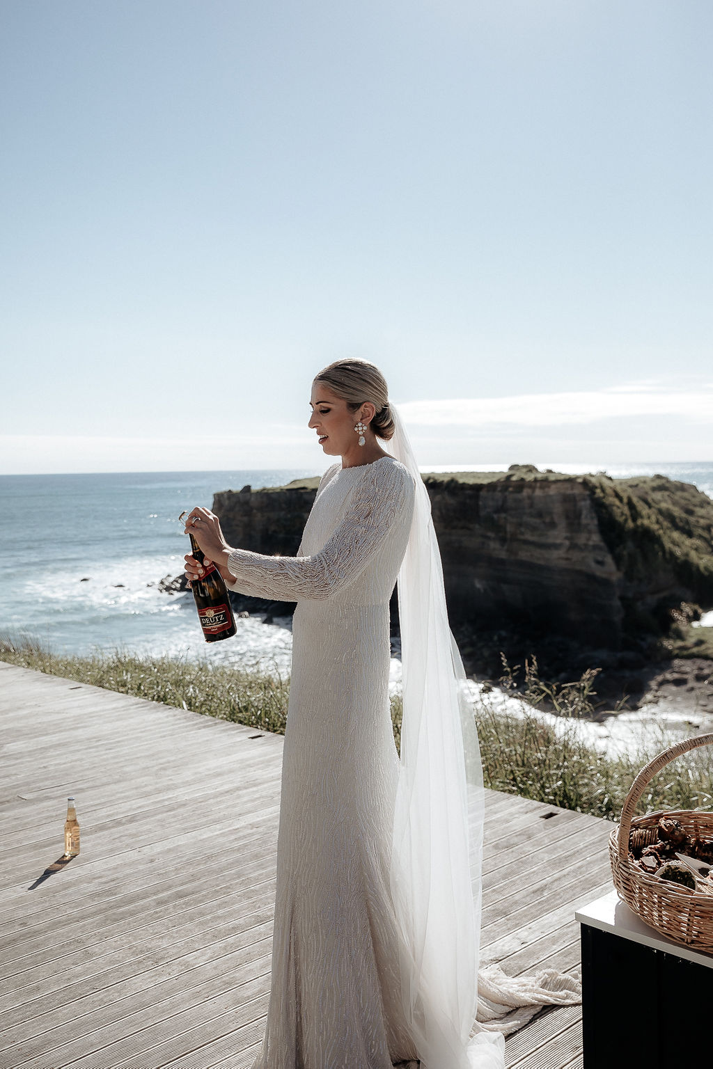 KWH real bride Hannah pops a bottle of bubbly with the New Zealand coast in the background. She dons the trendy sequined Margareta gown with low back and long sleeves.
