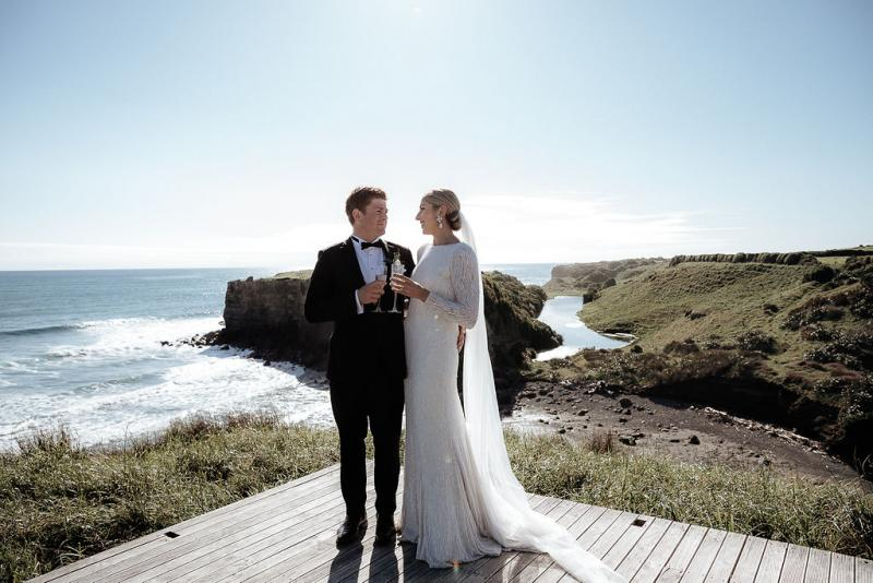 KWH real bride Hannah and Angus stand at the shoreline with drink in hand for a toast. She wears the modern beaded Margareta wedding dress with plunging back.
