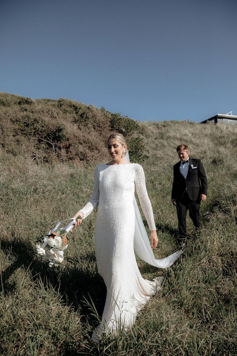 KWH real bride Hannah and Angus exchange looks while sharing a glass of champagne on the coast line. She wears the fit and flare beaded Margaretta wedding dress.