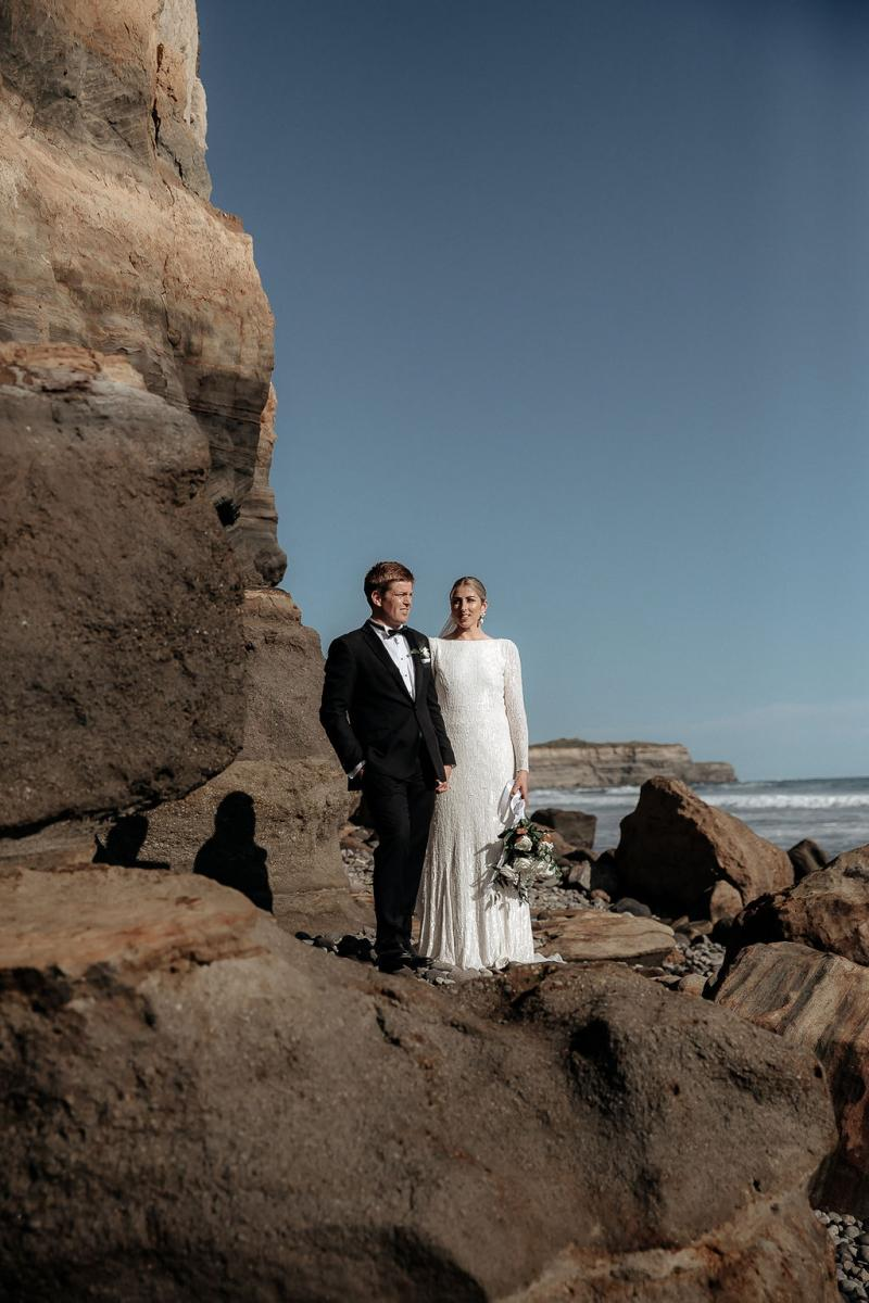Karen Willis Holmes Real Bride Hannah and Angus stand on a stone formation on the beach. She wears the effortless Margareta gown.
