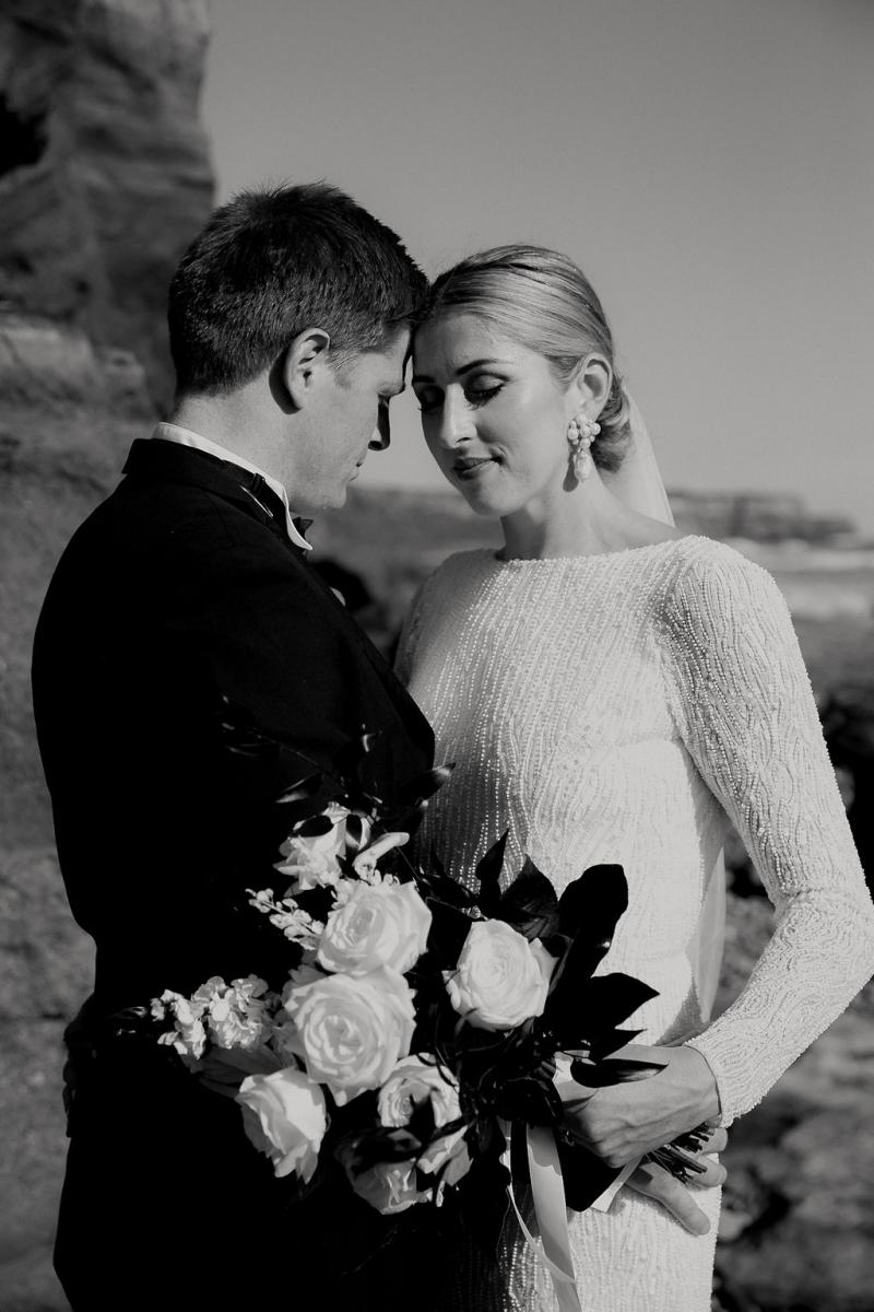 Black and white photo of KWH real bride Hannah and new husband Angus having a moment on the beach. She wears the high neckline Margaretta dress with long sleeves.