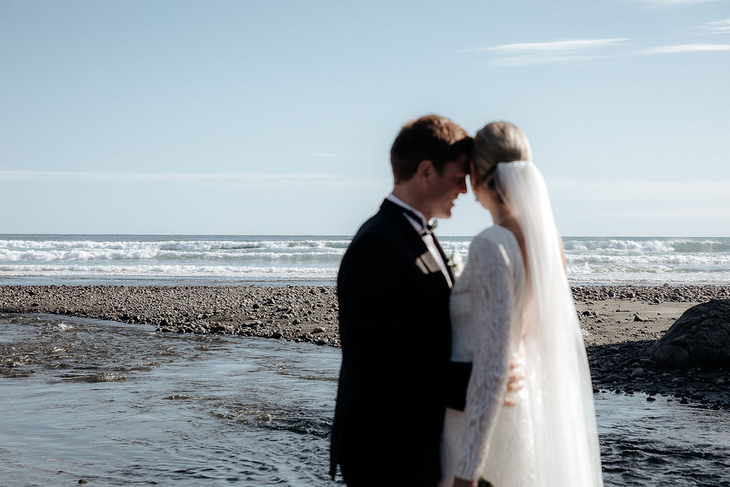 Real bride Hannah hugs Angus in front of the sea. She wears the beaded long sleeve Margaretta gown by Karen Willis Holmes.