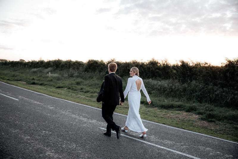 Real bride Hannah and Angus walk down the road. She wears a creation made by her brother; a while beaded dress with turtle neck and long sleeves.