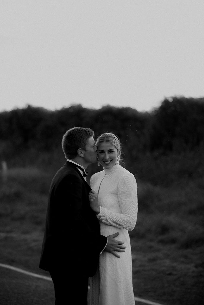 Black and white image of Real Bride Hannah and Angus standing together. She wears a custom designed gown made by her brother in NYC.