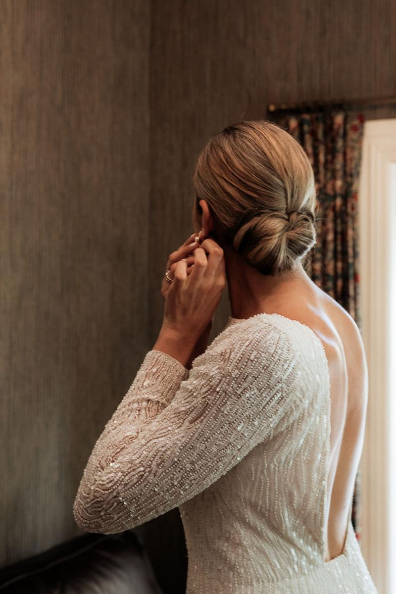 KWH Real bride Hannah adjusting her earring as she prepares for the day. She wears the simple yet stunning Margareta gown with high neckline.